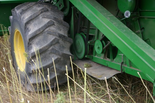To protect the combine and save clean up time, a heavy piece of rubber is clamped on the frame....